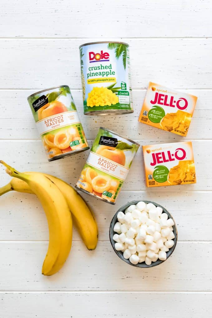 canned apricots, crushed pineapple, boxes of apricot gelatin, marshmallows and two bananas on a white surface