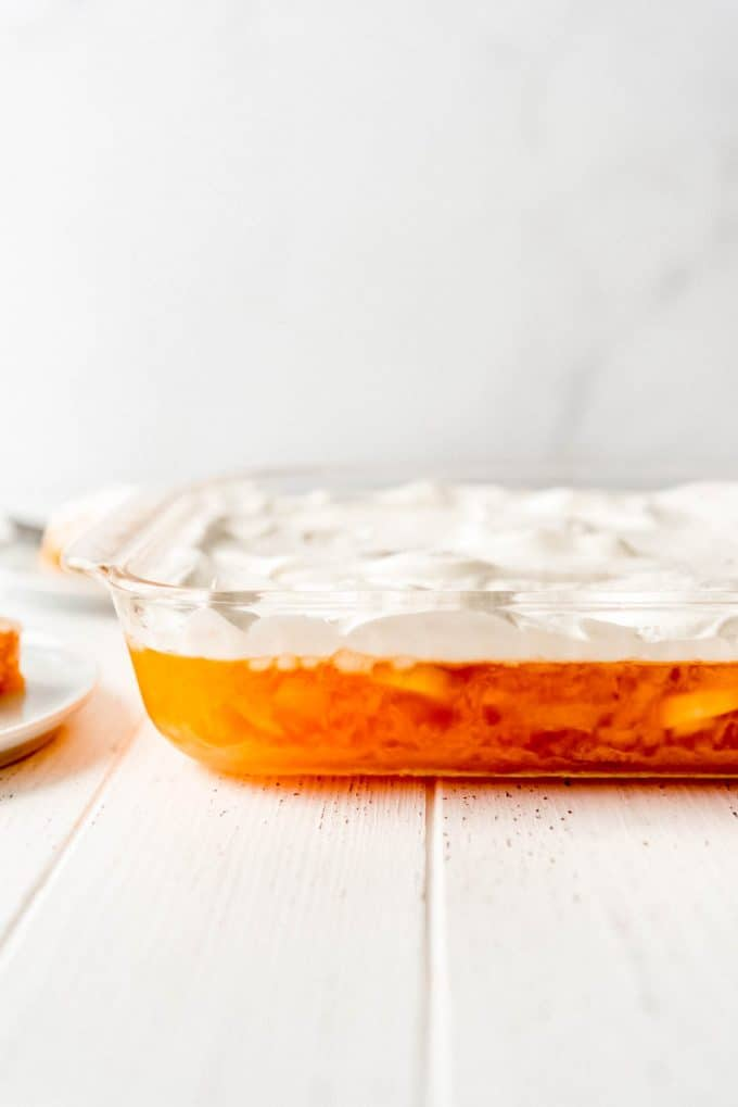 a side view of apricot jello in a glass baking dish