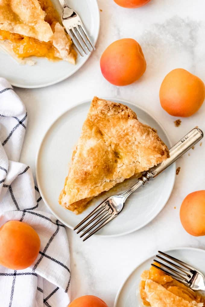 a slice of homemade apricot pie on a plate with a fork next to some fresh apricots