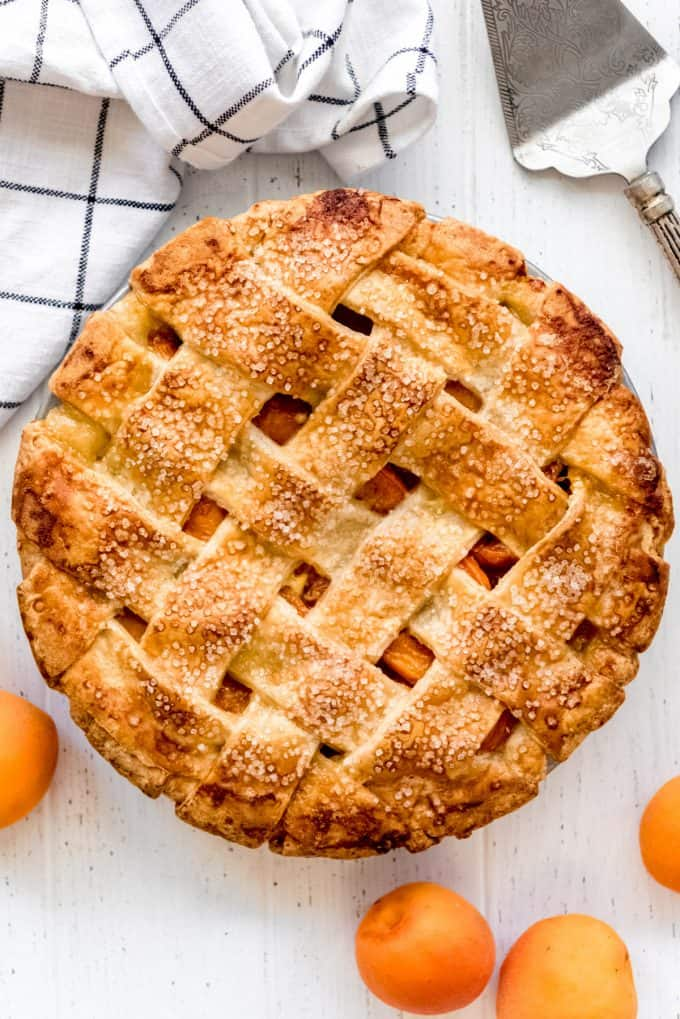 an overhead angle of an apricot pie with lattice crust next to some fresh apricots