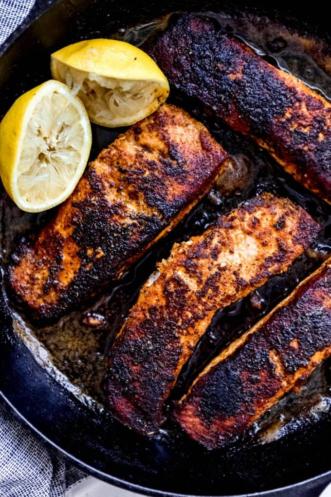 pan seared blackened salmon in cast iron skillet with lemon wedge