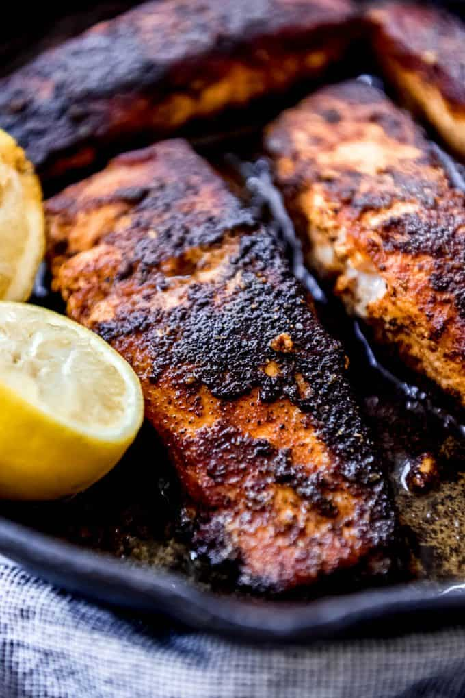 a close image of salmon fillets in a cast iron pan with a blackened crust