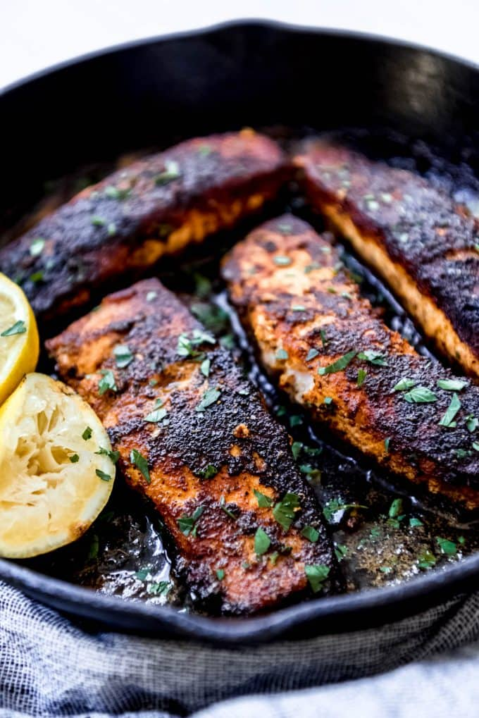 blackened salmon in cast iron skillet topped with fresh lemon juice and herbs