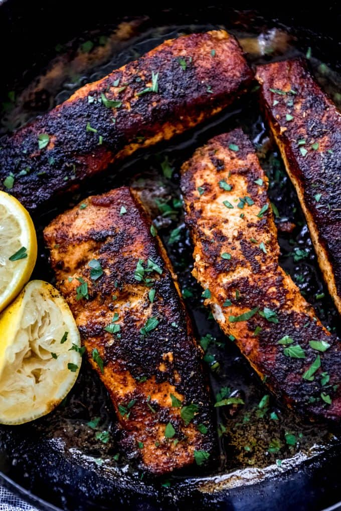 Blackened salmon fillets in cast iron skillet topped with fresh herbs