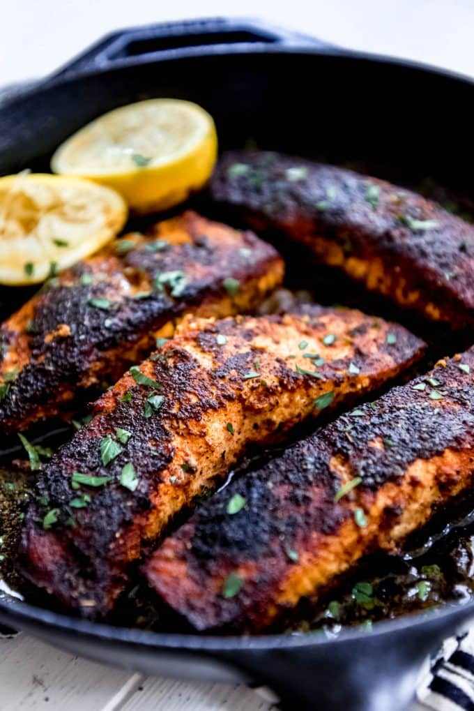 pan seared blackened salmon fillets in a cast iron pan with lemons