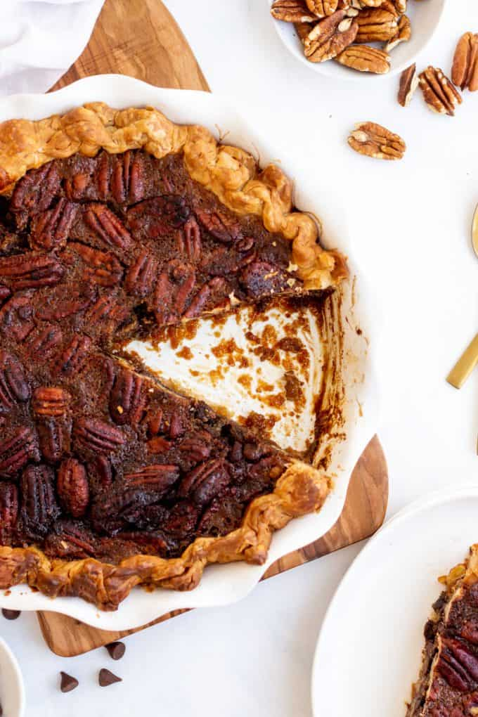 a slice of chocolate pecan pie cut out of a white pie dish