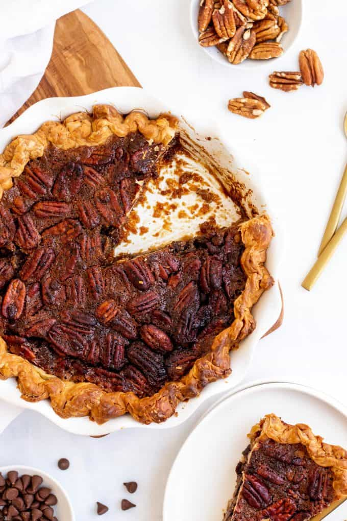 a whole chocolate pecan pie with a slice cut out of it