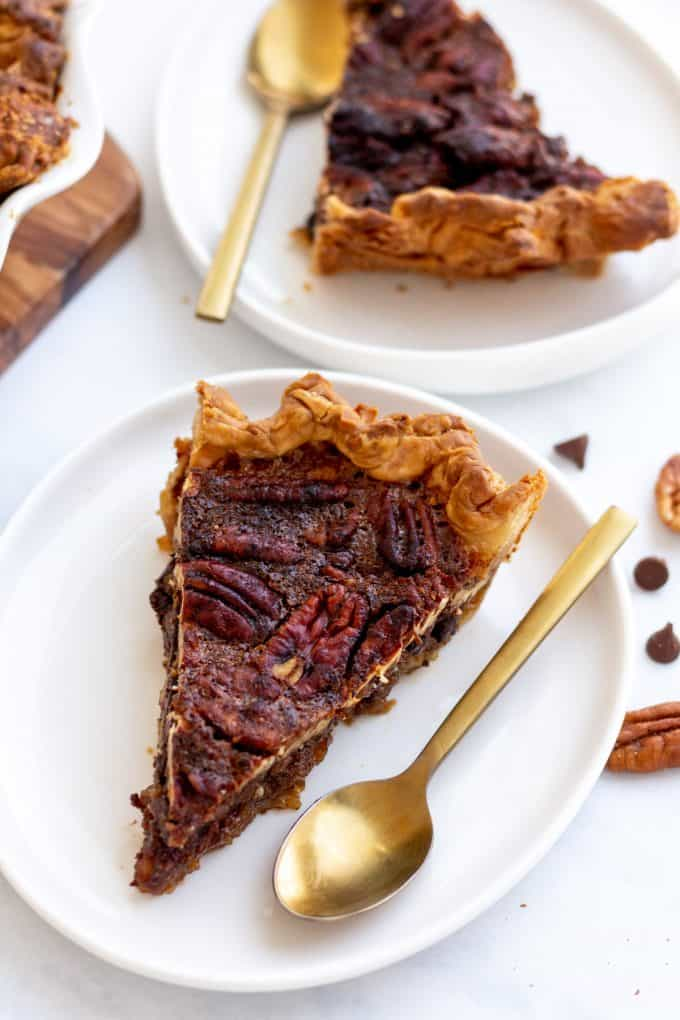 slices of chocolate pecan pie served on a white pie plate with a gold spoon
