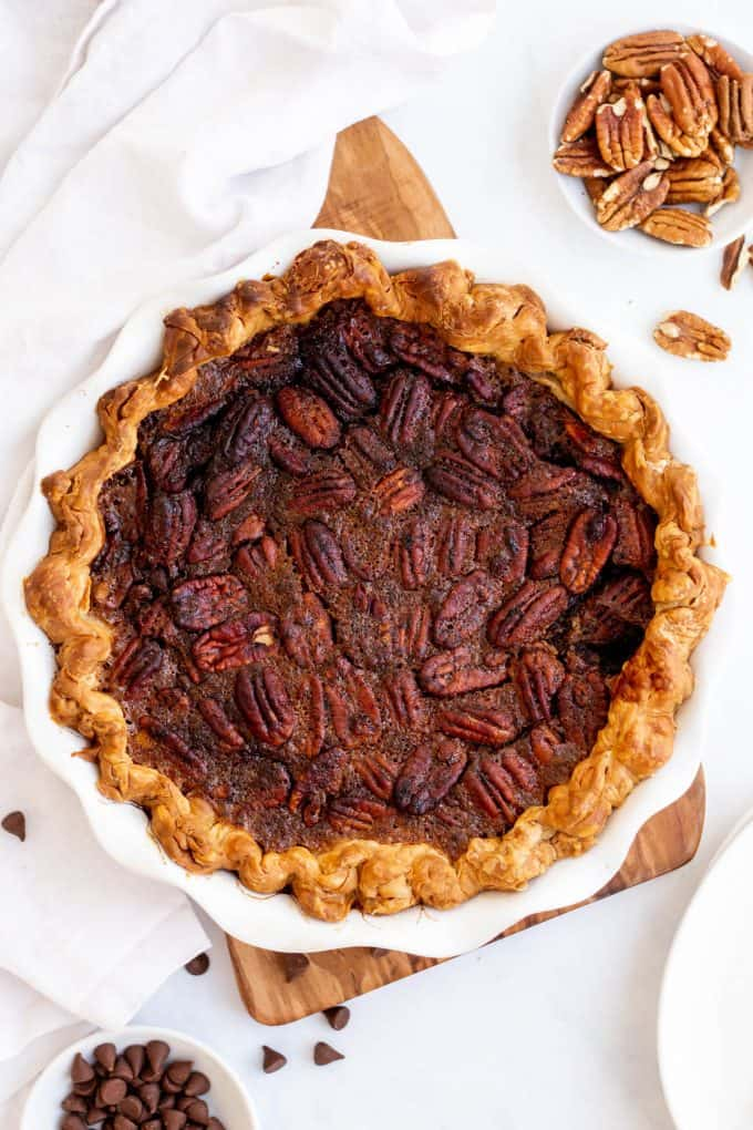 a whole chocolate pecan pie in a white pie dish