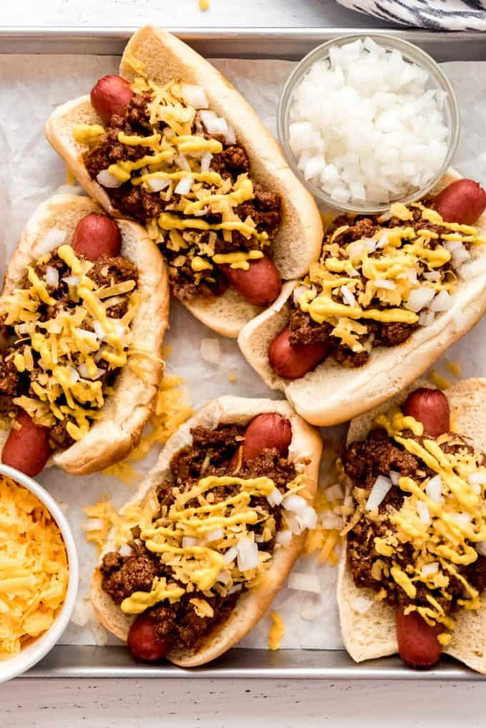 Coney Island hot dogs assembled on a baking sheet with a bowl of cheese and a bowl of onions