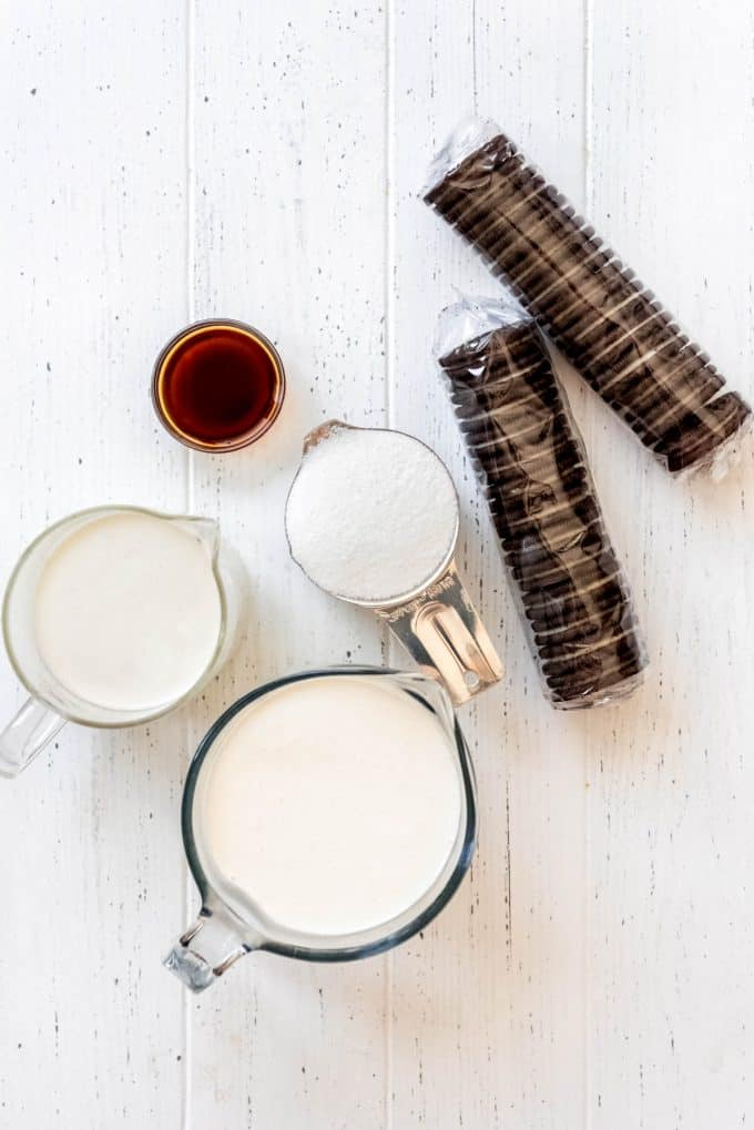 measuring cups of milk, heavy cream, sugar, vanilla extract and packages of Oreos on a white table