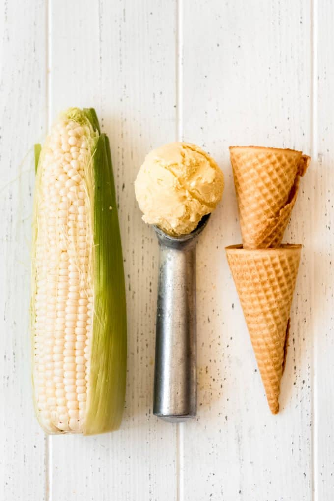 a scoop of corn ice cream on an ice cream scoop next to sugar cones and an ear of corn