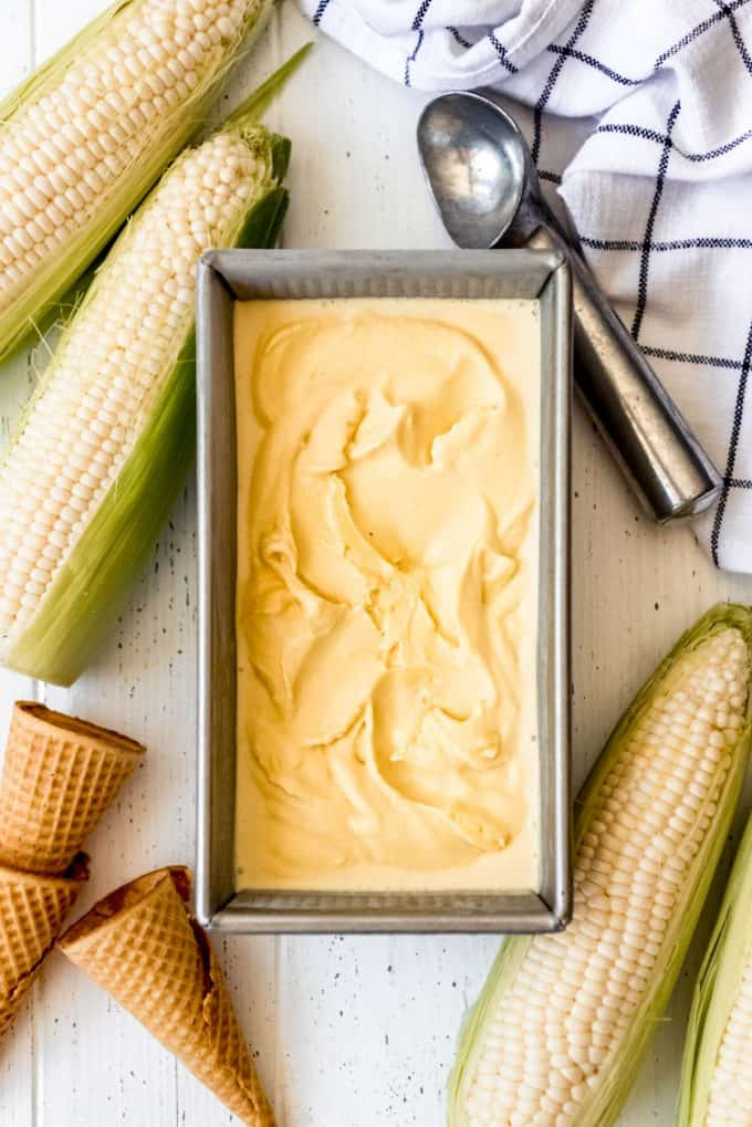 a bread pan filled with corn ice cream next to corn on the cob and sugar cones