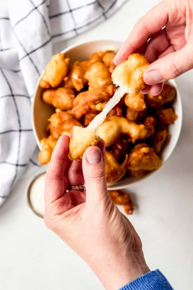 hands stretching apart a fried cheese curd