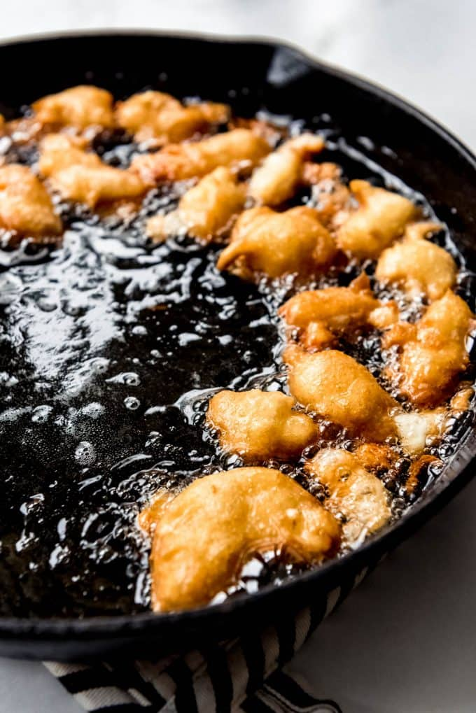 battered fresh cheese curds frying in hot oil in a cast iron skillet