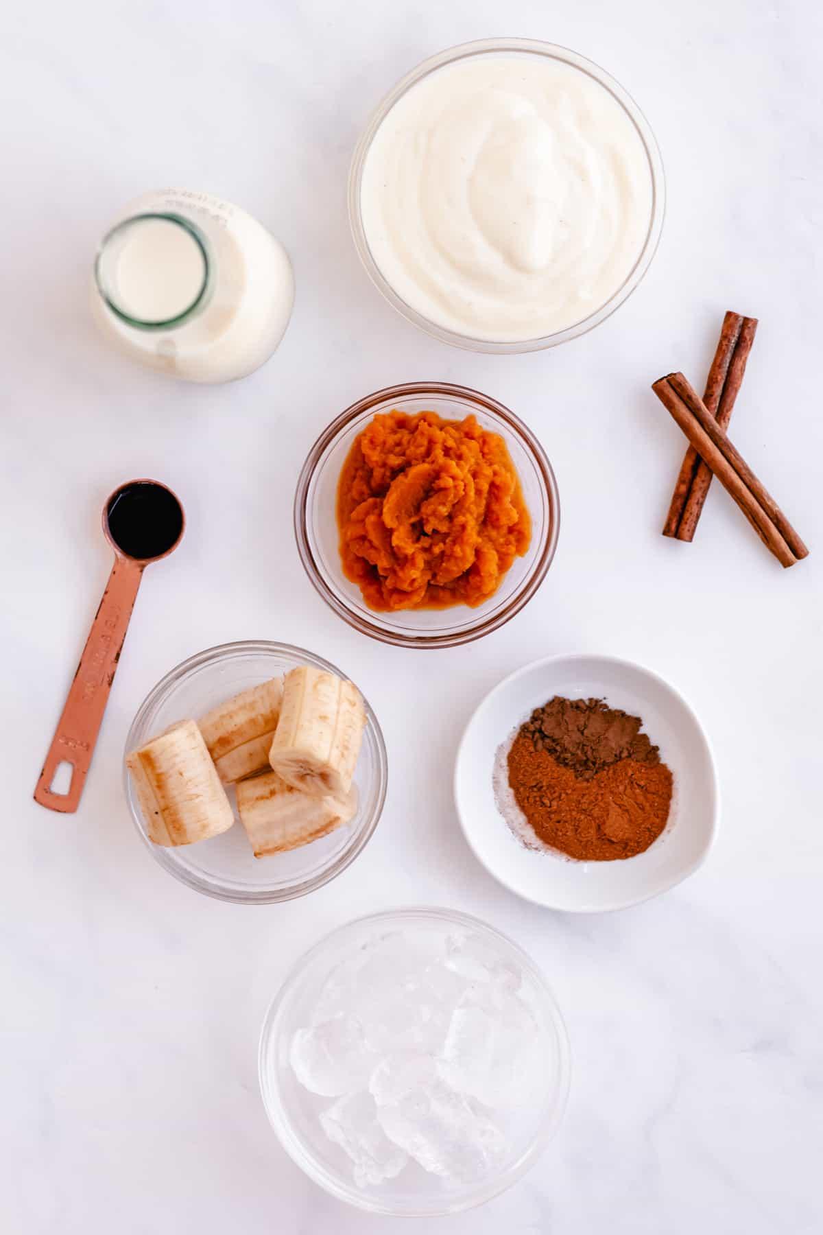 yogurt, milk, pumpkin puree, cinnamon sticks, banana, pumpkin pie spices on a counter