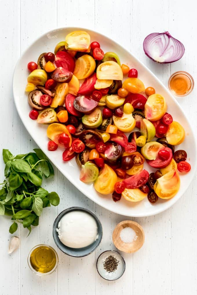 ingredients for an heirloom tomato salad on a white surface