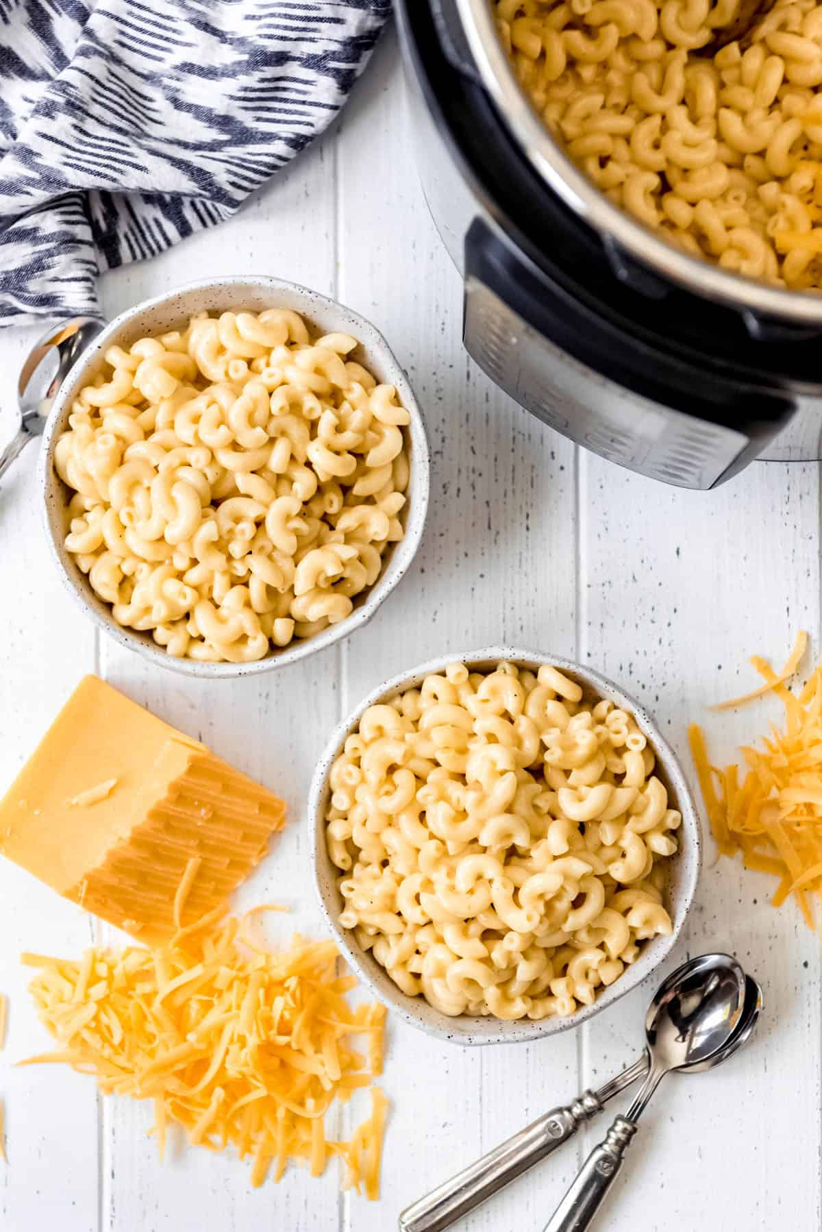 two bowls of macaroni and cheese next  to a block of cheddar cheese.