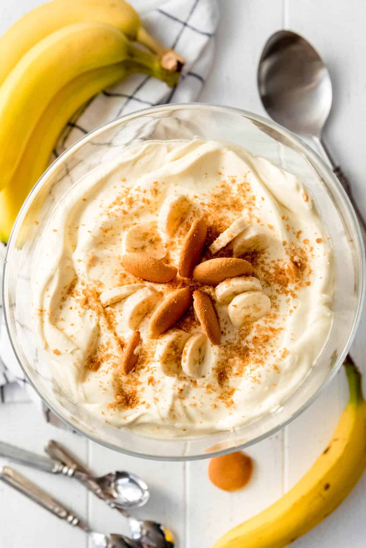 Magnolia Bakery Banana Pudding Trifle on white counter top with whole bananas and a spoon