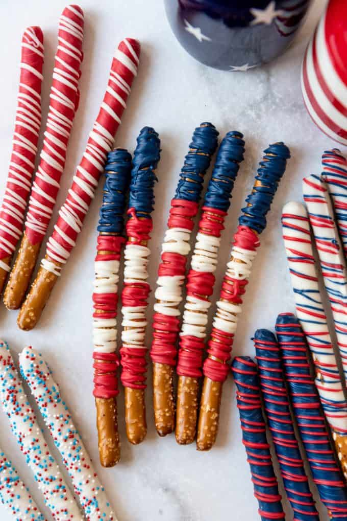 pretzel rods decorated with melted white chocolate in patriotic colors