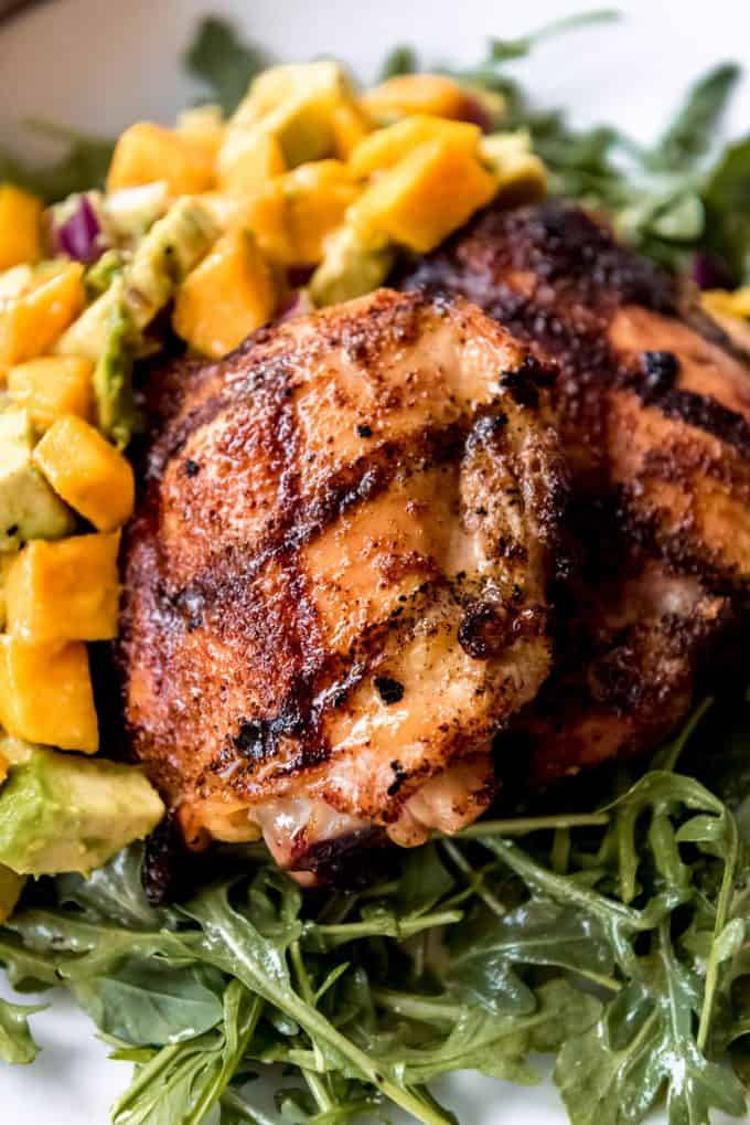 a close image of a grilled chicken thigh with spice rub and honey glaze