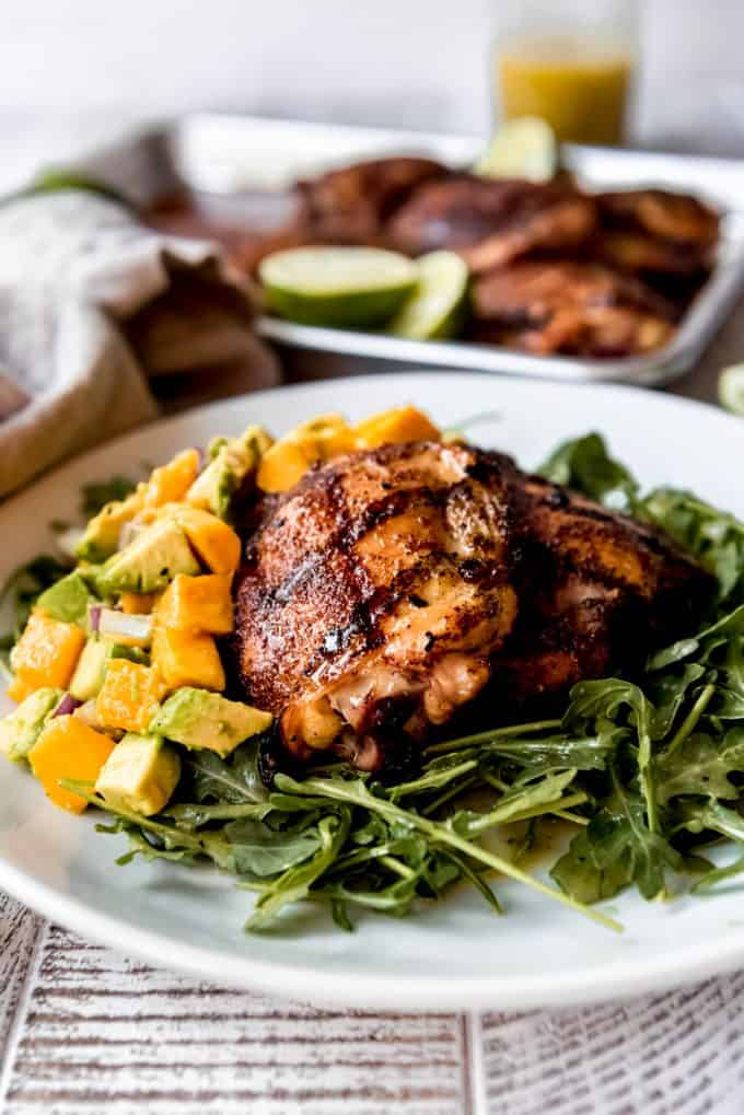 a plate of arugula salad, mango salsa, and grilled spicy honey chicken