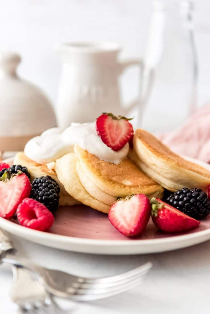 a plate full of three fluffy Japanese pancakes with whipped cream and fresh fruit