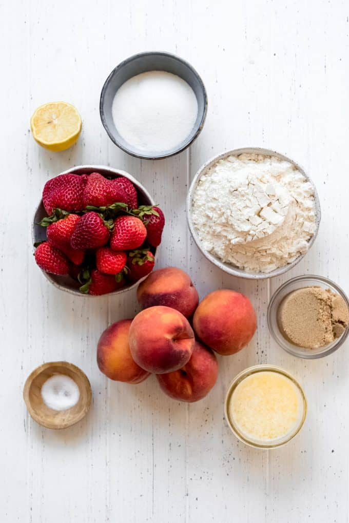 ingredients for a strawberry peach crumble on a white surface