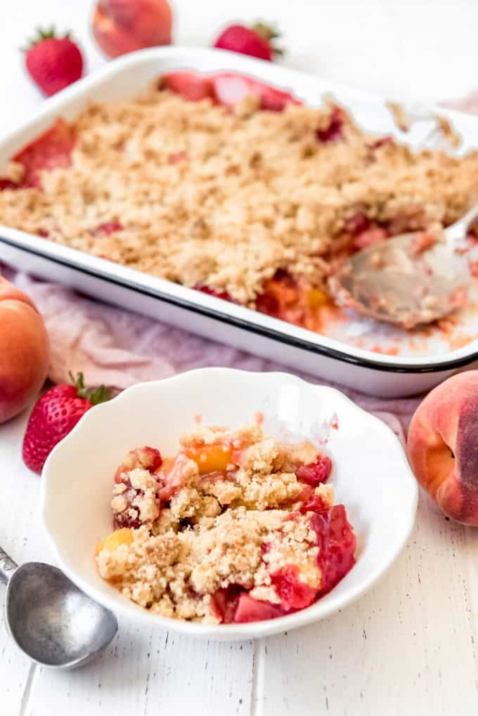 a scoop of strawberry peach crumble in a bowl in front of a baking dish