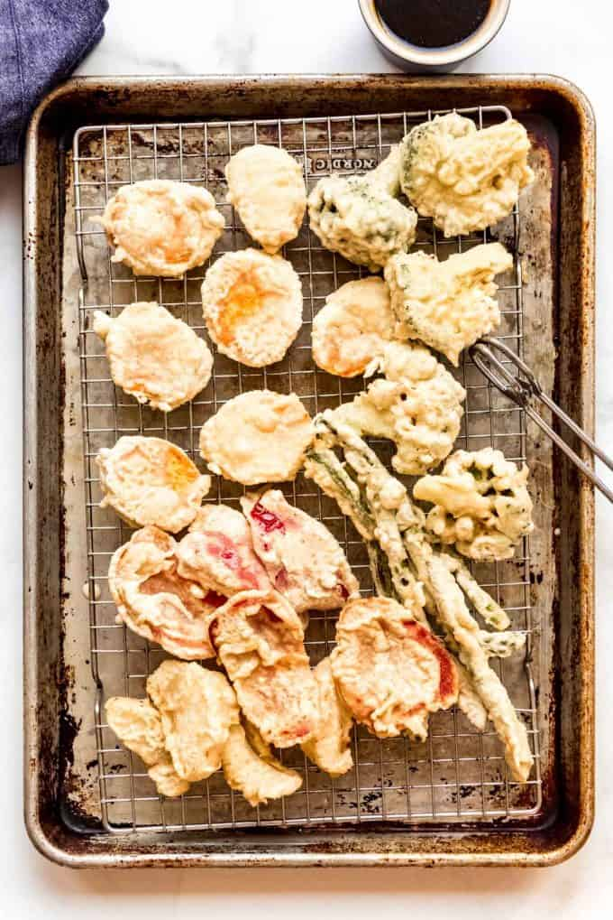 fried Japanese vegetable tempura on a wire rack over a baking sheet