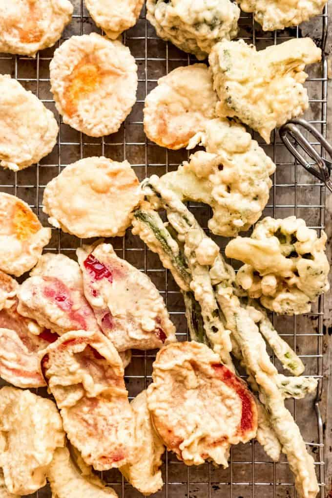 homemade vegetable tempura draining on a wire rack over a baking sheet