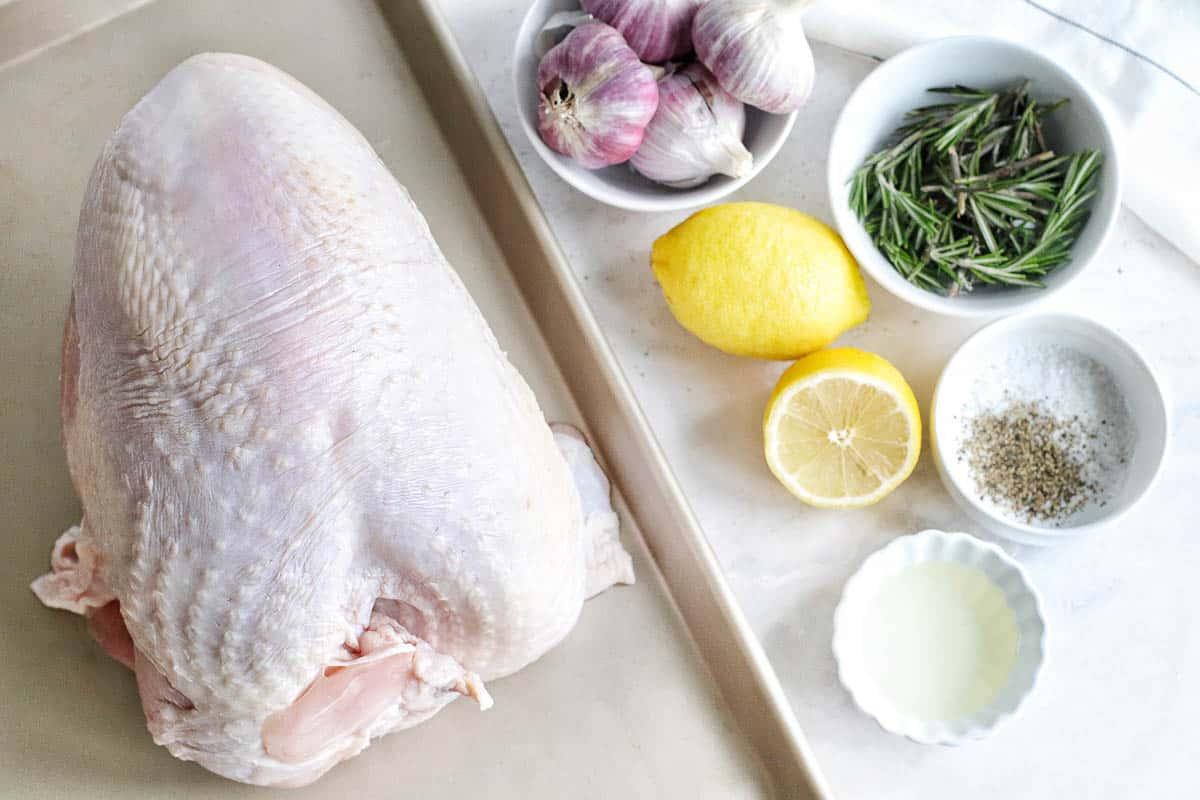 raw turkey breast on a baking sheet, whole bulbs of garlic, lemons, fresh rosemary, salt, pepper, lemon juice