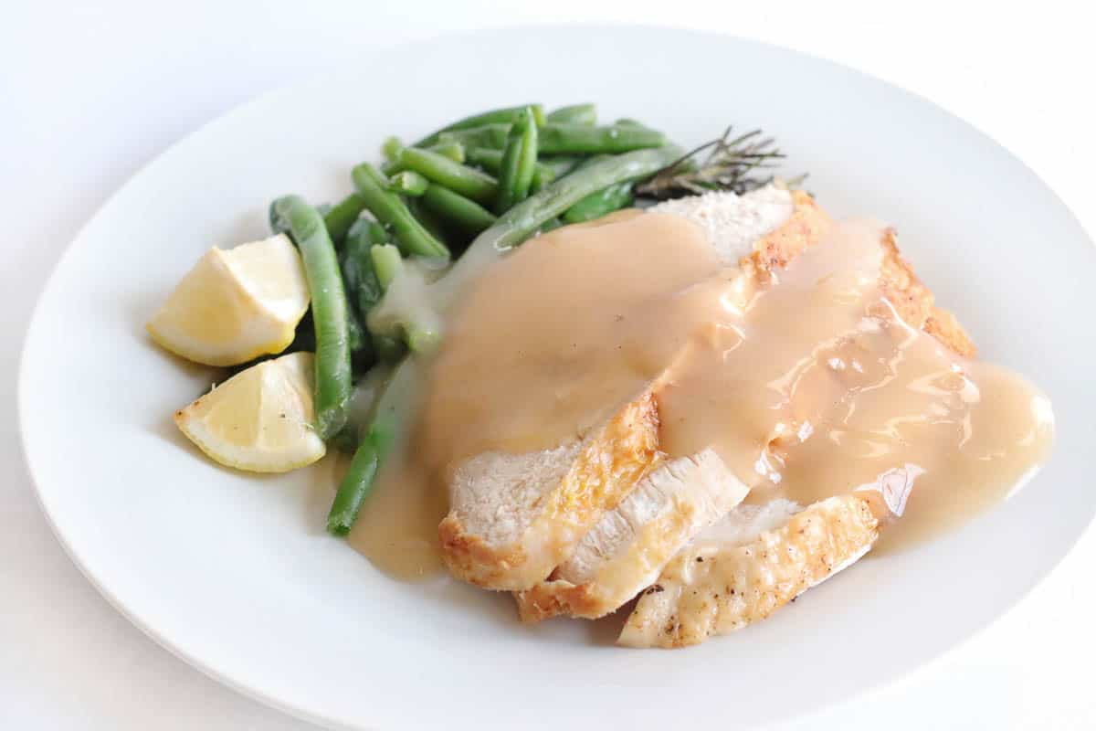 Slices of turkey breast cooked in the air fryer, covered with gravy and a side of green beans