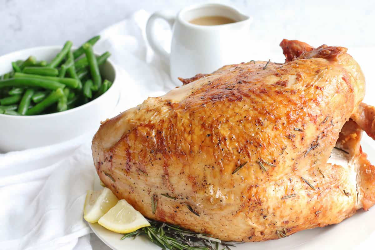 Air Fryer Turkey Breast on a white plate with a side of gravy and green beans
