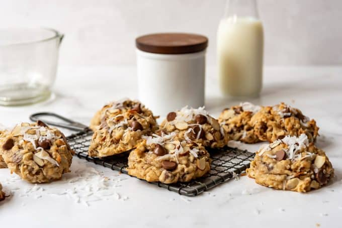 almond joy cookies on a wire rack in front of a white jar and a bottle of milk
