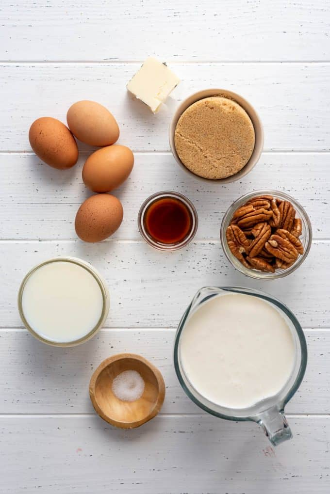 milk, cream, eggs, vanilla, salt, butter, brown sugar, and pecans in separate containers on a white surface