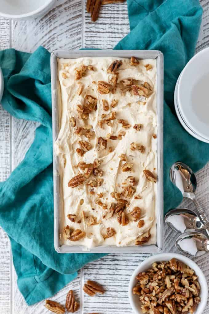 a bread pan full of butter pecan ice cream with toasted chopped pecans sprinkled on top