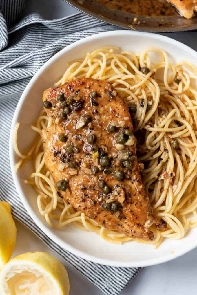a piece of lightly breaded chicken in a lemon caper sauce over pasta