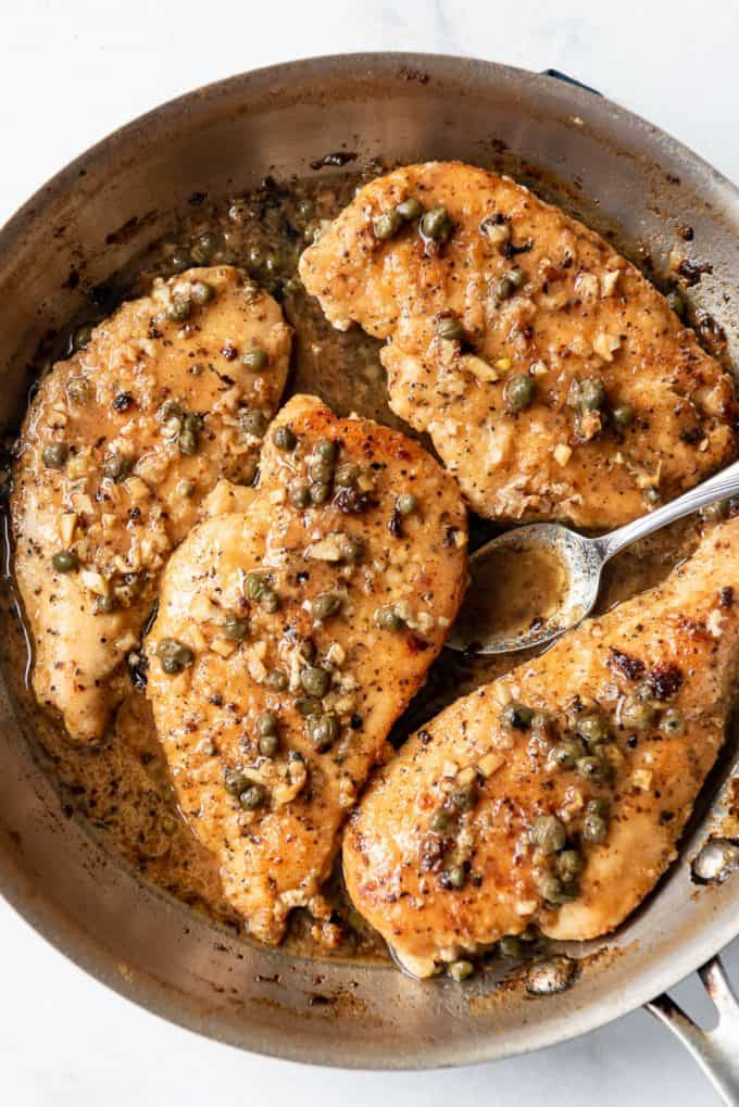 pan fried chicken breasts with a lemon garlic caper pan sauce in a pan