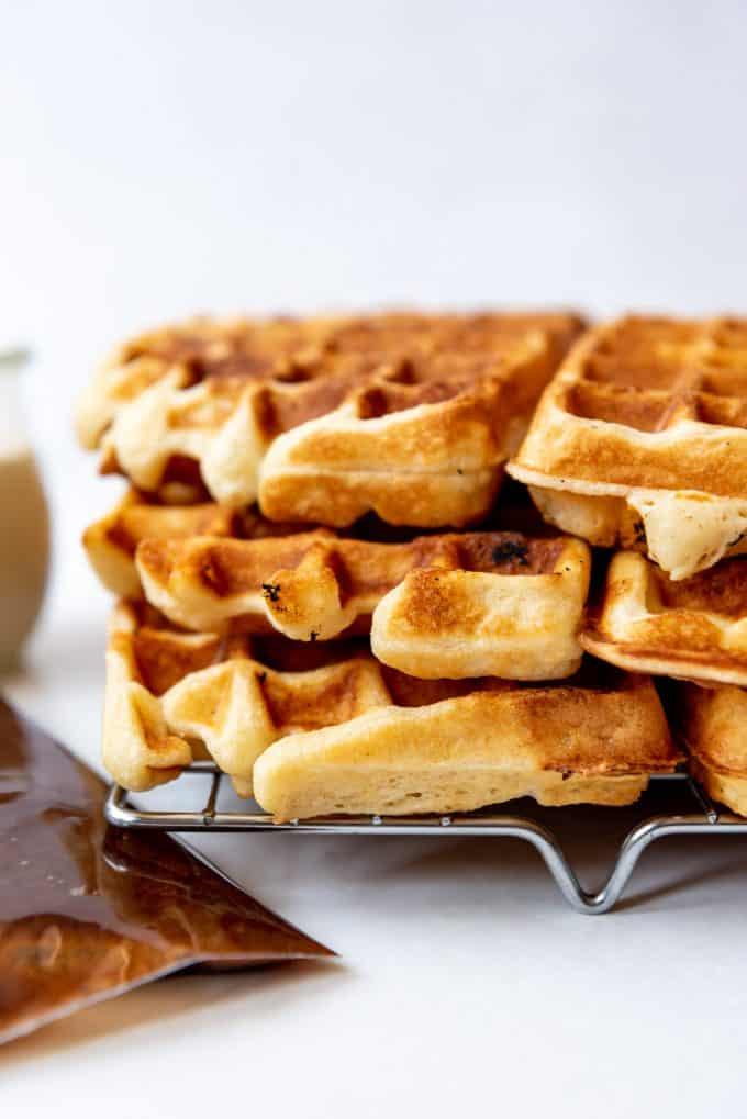 a stack of fluffy homemade buttermilk waffles on a wire rack