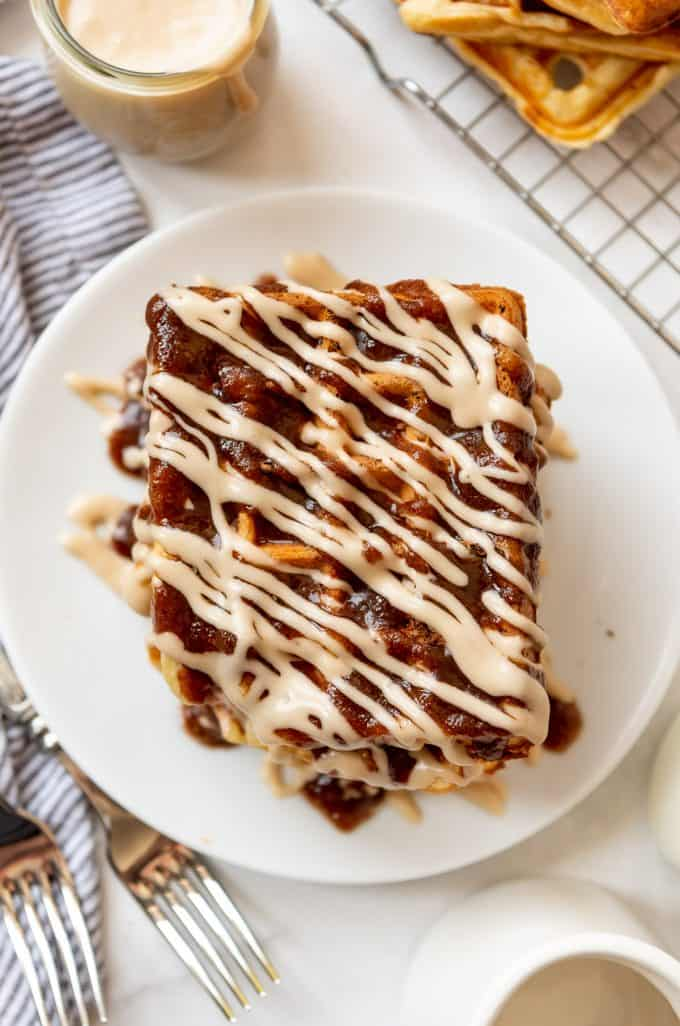 a buttermilk waffle drizzled with a brown sugar glaze and a maple cream cheese icing on a white plate