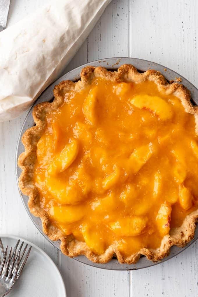 a whole fresh peach pie in a metal pie tin