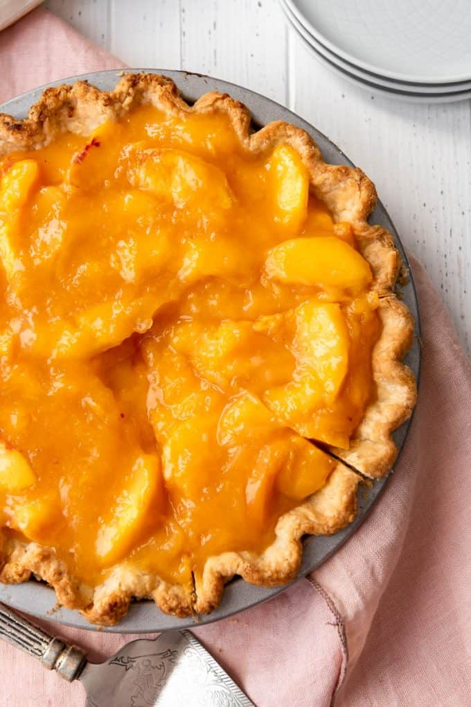 a peach pie with two slices cut into it on a pink linen napkin