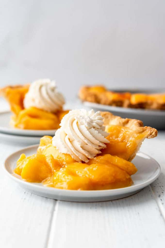 slices of fresh peach pie topped with whipped cream on plates