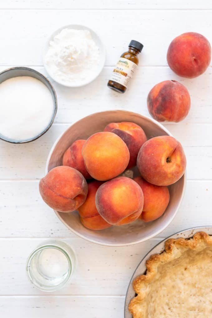 ingredients for fresh peach pie include peaches, sugar, cornstarch, almond extract, water, and a pie crust
