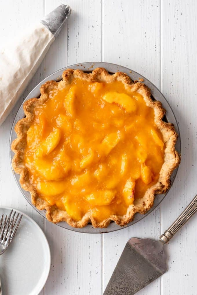 a homemade peach pie in a blind baked crust next to a piping bag filled with whipped cream