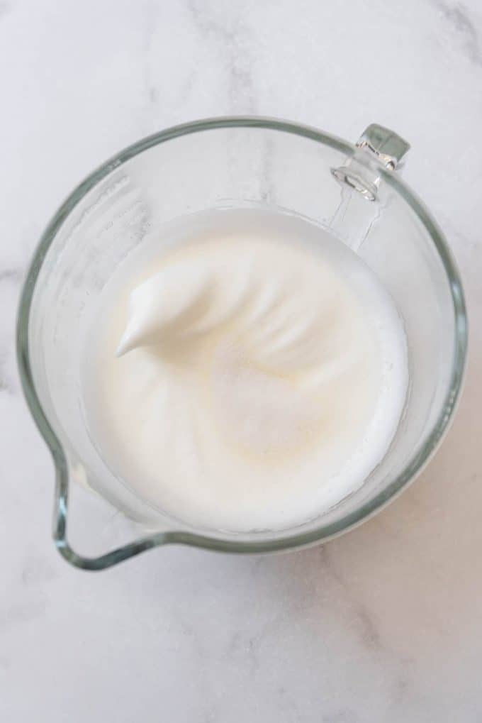 Egg whites beaten to soft peaks with sugar being added.