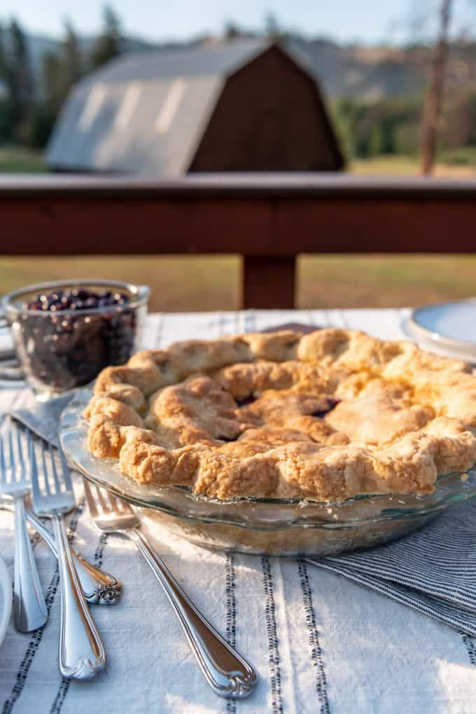 a huckleberry pie in a glass pie plate in front of a barn in Montana