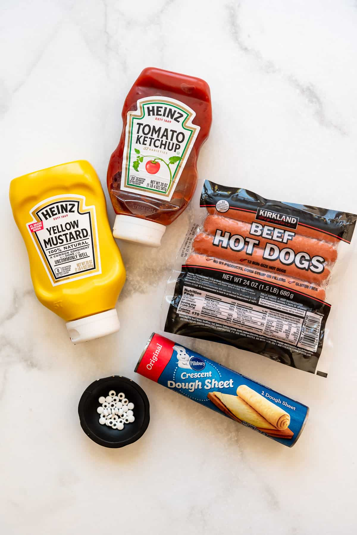 ketchup, mustard, hot dogs, a tube of crescent roll dough sheets, and eyeball sprinkles.