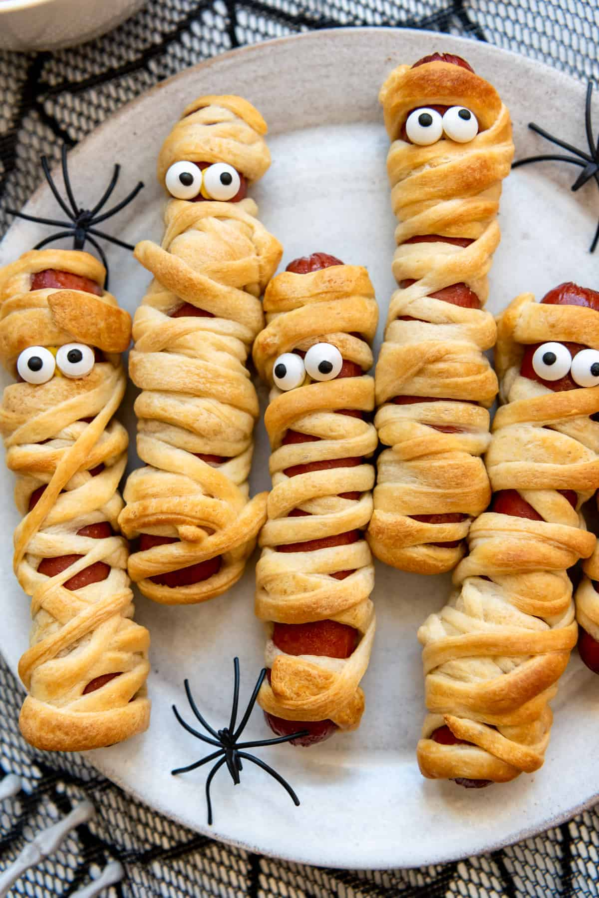 a close image of beef hot dogs wrapped in crescent roll dough to look like mummies for Halloween.